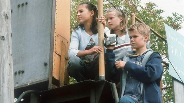 Die Pfefferkörner Jana (Anna-Elena Herzog, li.), Natascha (Vijessna Ferkic, Mi.) und Fiete (Julian Paeth, re.) sind einem Umweltskandal auf der Spur. Heimlich beobachten sie, wie giftige Schwefelsäure in falschen Kanistern auf eine Barkasse verladen wird. | Rechte: NDR/Baernd Fraatz