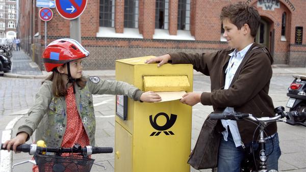 Marie (Nina Flynn) und Laurenz (Tim Tiedemann) wollen ihre Unterschriftensammlung einwerfen, nicht ahnend dass sich im Postkasten eine heimtückische Bombe befindet. | Rechte: NDR/Romano Ruhnau