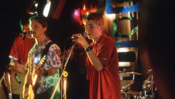 Fiete (Julian Paeth, re.) überascht Natascha zum Geburtstag mit einem Live-Song, den er gemeinsam mit Leadsänger Ferry (Norman Nitzel, li.) von Andrejs neuer Nachwuchsband singt. | Rechte: NDR/Baernd Fraatz