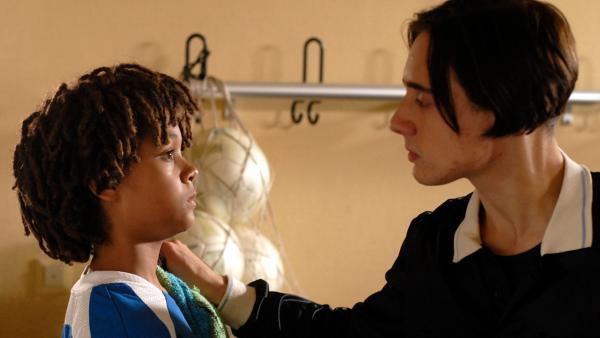 Ein junger Mann in Schiedrichter-Trikot packt Themba (Coco Nima) an der Schulter | Rechte: NDR/Romano Ruhnau