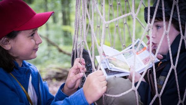 Jale (Ava Sophie Richter, links) steht lächelnd vor Timo (Malon Stahlhut) der in einem Netz steckt. | Rechte: NDR/Studio HH Foto: Boris Laewen