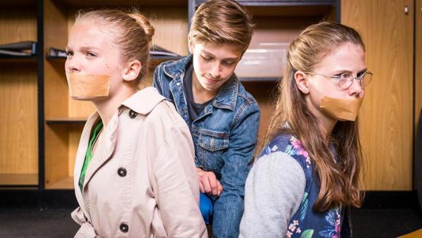 Till (Otto von Grevenmoor) kniet zwischen Stella (Zoe Malia Moon, links) und Pinja (Sina Michel), die ein Klebeband über den Mündern haben. | Rechte: NDR/Studio HH Foto: Boris Laewen