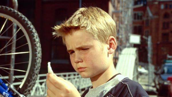 Fiete steht vor einem Fahrradreifen und betrachtet etwas in seiner Hand | Rechte: NDR