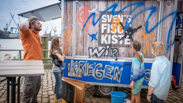 Kira, ihr Vater, Nele und Levin schauen sich die zerstörte Fischbude an. | Rechte: NDR/Studio HH Foto: Boris Laewen