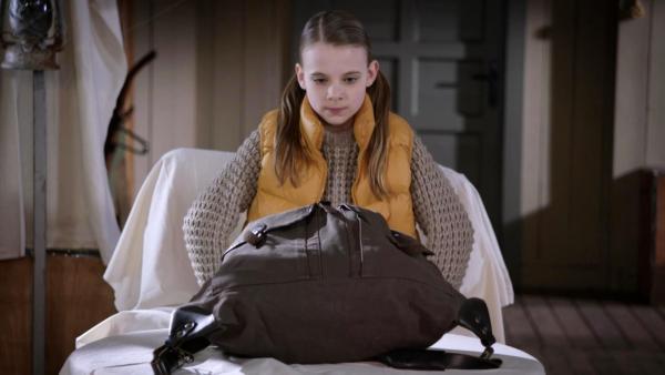 Szene aus Die Pfefferkörner Folge 186: Ein kleines Mädchen schaut sich einen großen Rucksack an. | Rechte: NDR