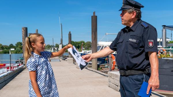 Clarissa überreicht dem Polizisten ein Bild, auf dem das Gesicht eines Mannes zu erkennen ist. | Rechte: NDR/Letterbox Foto: Boris Laewen