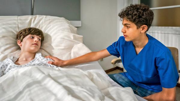 Tarun legt einem Jungen, der in einem Krankenhausbett liegt, eine Hand auf die Schulter. | Rechte: NDR/Letterbox Foto: Boris Laewen