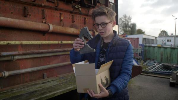 Benny hält ein Karton und ein Figur in der Hand. | Rechte: NDR