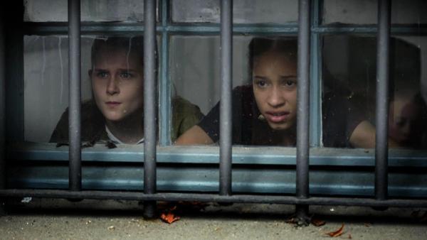 Lisha und Mia schauen durch ein Fenster vor dem Metalgitter ist. | Rechte: NDR