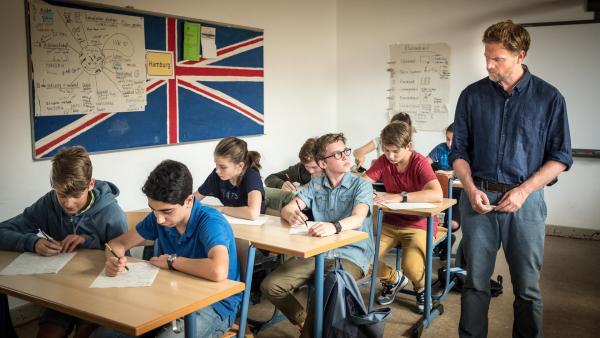 Lehrer Martin Schulze (Janek Rieke) steht neben Benny (Ruben Storck, Mitte) in der Klasse. | Rechte: NDR/Studio JJ Foto: Boris Laewen