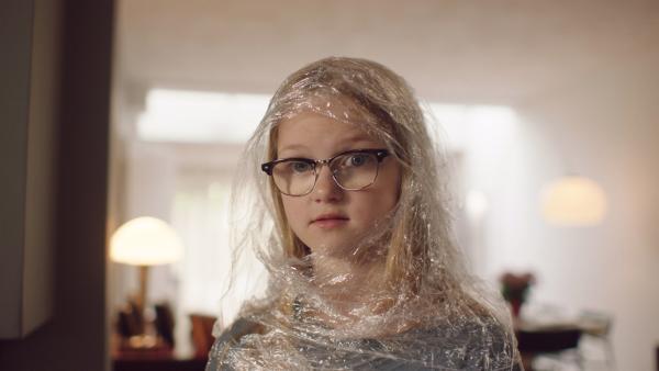 Im selbstgemachten Schutzanzug sieht Floor (Bobbie Mulder), dass Margreet viele Geschenke bekommt, weil sie krank ist. | Rechte: NDR/NL Film