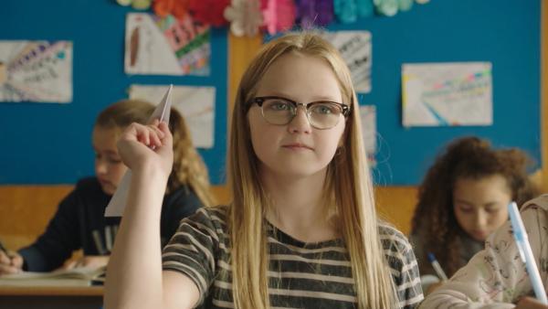 In einer Rückblende wirft Floor (Bobbie Mulder) einen Papierflieger durch die Klasse. Sie möchte Wouter fragen, ob er ihr Freund sein möchte. Doch der Flieger landet auf Freeks Tisch. | Rechte: NDR/NL Film