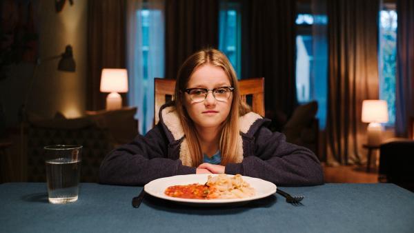 Floor (Bobbie Mulder) sitzt am Tisch während Kees über ihr Abendessen vloggt.   Rechte: NDR/NL Film/Maurice Trouwborst