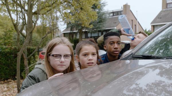 Vier Kinder verstecken sich hinter einem Auto. | Rechte: NL Film