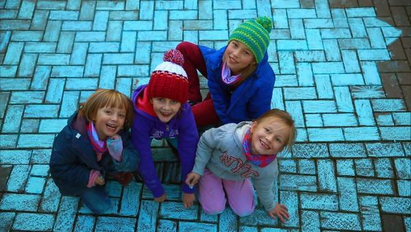 Kinder malen mit blauer Straßenkreide den Bürgersteig an. | Rechte: WDR