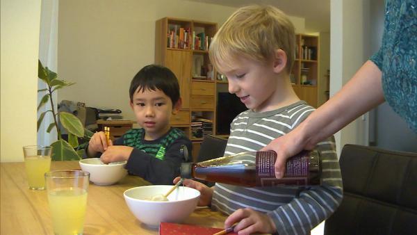 Henry und Jack essen zusammen chinesische Maultaschen, natürlich mit Stäbchen.   Rechte: WDR