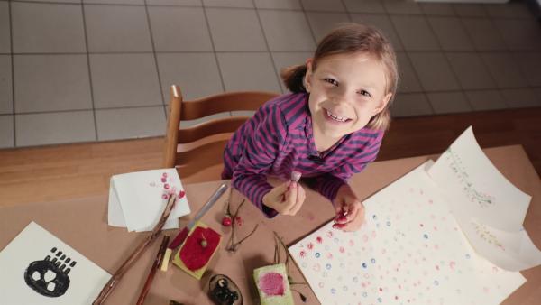 Olivia bastelt sich aus Kartoffeln und Blumenfrüchten Stempel und macht damit kreative Bilder. | Rechte: WDR