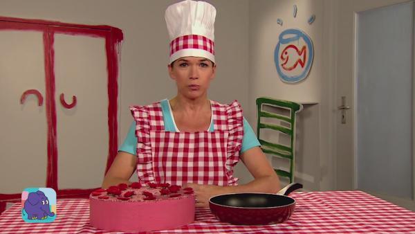 Anke sitzt mit einer Kochmüzue und einer rotkarierten Küchenschürze vor einem Tisch. Auf dem Tisch steht ein Erdberkuchen und eine Pfanne. | Rechte: WDR