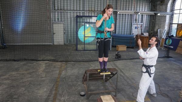 Moderatorin Laura Knöll testet die Stabilität eines Holzbretts. Taekwondo-Kämpfer Jan Schrumm sichert sie dabei. | Rechte: ZDF/Hannah Jacoby