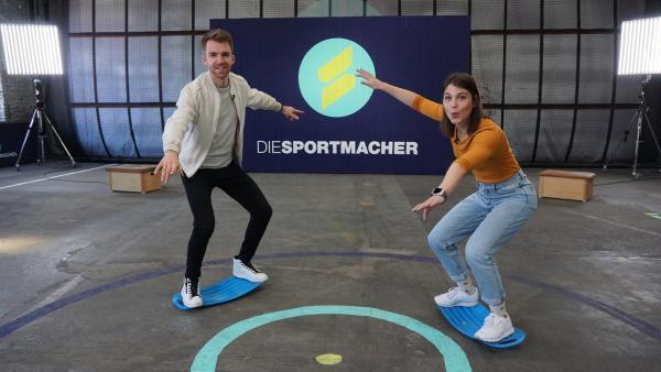 Das Moderatorenteam Laura und Stefan machen Trockenübungen für's Windsurfen, um ihre Balance zu trainieren. Keine leichte Aufgabe!   Rechte: ZDF/Annalena Renneisen/Fabian Gratzla