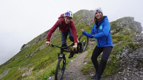 Tom Öhler (links) springt mit seinem Bike und Laura (rechts) steht nebendran. Die beiden stehen auf einem Berg. | Rechte: ZDF