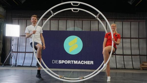 Stefan (links) und Birte (rechts) sitzen jeweils auf einer Seite eines Rhönrades.   Rechte: ZDF