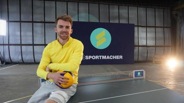 Stefan sitzt mit einem Volleyball auf einer Tischtennisplatte. | Rechte: ZDF