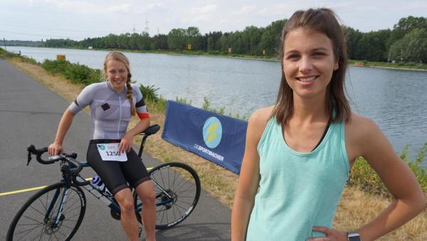 Caro (links) sitzt auf ihrem Rad und hält ihre Startnummer in der Hand. Laura (rechts) steht  im Sportoufit vor ihr. | Rechte: ZDF