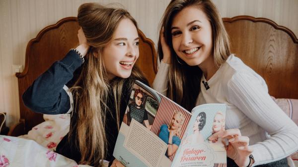 Pia und Kassandra suchen in einer alten Zeitschrift nach einer passenden Vintage-Frisur. | Rechte: ZDF/Phil Janssen