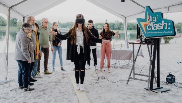 Bei der letzten entscheidenden Aufgabe im Finale muss jeweils einer der beiden Teams mit einer virtuellen Brille über einen Holzbalken balancieren.   Rechte: ZDF/Phil Janssen