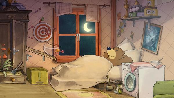 Dr. Brumm liegt zufrieden im Bett, nachdem er für das zu lange Brett eine einfache Lösung gefunden hat.   Rechte: rbb/WunderWerk/TRIKK 17