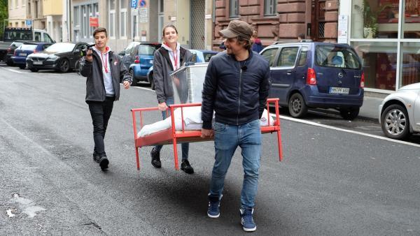 Auf der Suche nach einem Schlafplatz: Tupac, Sarah und Moderator Tommy Scheel tragen das rote Bett durch Kölns Straßen. | Rechte: ZDF/Annalena Renneisen