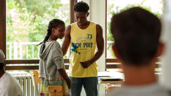 Etwas eifersüchtig beobachtet Yassir (Julius Göze), wie Aminata (Jodyna Basombo) Nebay (Stephen Owusu-Sekyere) eine selbst gebastelte Blume schenkt. | Rechte: ZDF/Conny Klein