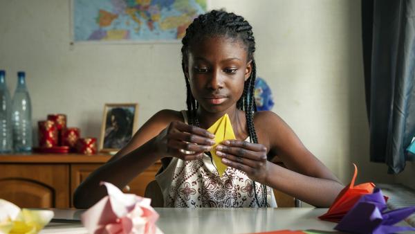 Die Kunst des Blumenfaltens ist das einzige, das Aminata (Jodyna Basombo) von ihrer verloren gegangenen Mutter geblieben ist. | Rechte: ZDF/Conny Klein