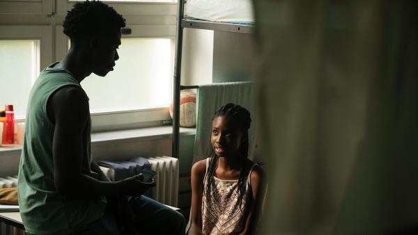 Aminata (Jodyna Basombo) gesteht ihrem großen Freund Nebay (Stephen Owusu-Sekyere), dass sie Angst davor hat, ihren kriminellen Bruder zur Rede zu stellen.   Rechte: ZDF/Conny Klein