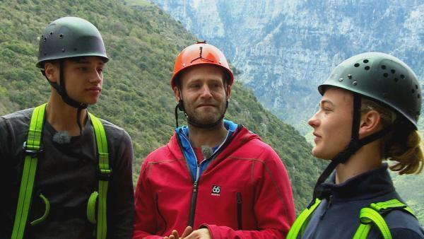 Tobi (Mi.) erläutert die nächste Herausforderung: Eine senkrechte Felswand soll hochgeklettert werden.   Rechte: hr/E+U TV Film- und Fernsehproduktion