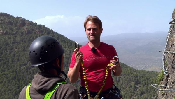 Coach Tobi erklärt den Gurt und die Sicherung, bevor die Sechs an den Klettersteig an der Steilwand dürfen. | Rechte: hr/E+U TV Film- und Fernsehproduktion