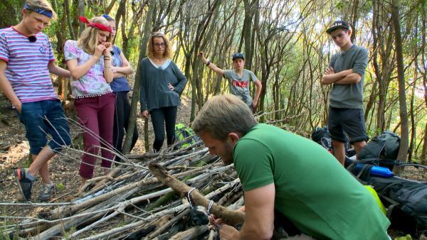Tobi zeigt den Abenteurern, wie sie die Äste möglichst stabil zusammenknoten.