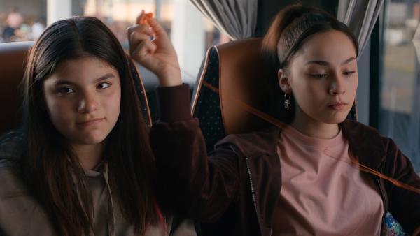 Zerda (l. Laila Mascher) sitzt auf der Busfahrt neben ihrer neuen Freundin Leyla (r. Aleyna Kus) und hat Mia ganz vergessen. | Rechte: ZDF/Studio Zentral