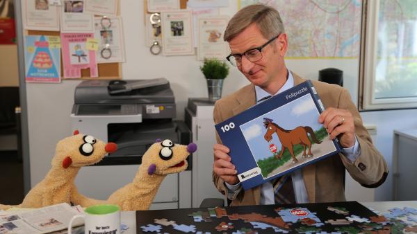 Der Kommissar (Michael Kessler) präsentiert den Erdmännchen sein Polizeipferdepuzzle. | Rechte: NDR/bigSmile
