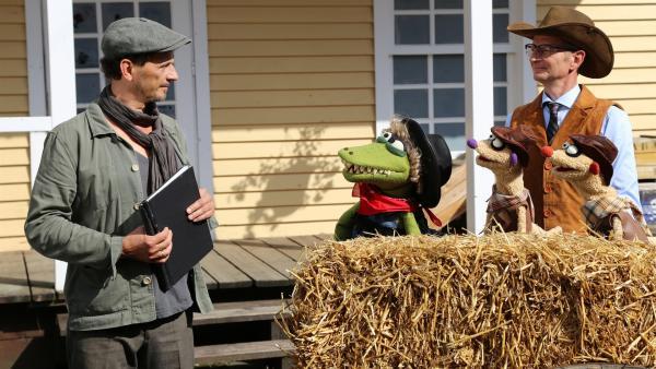 Der Regisseur (Jörg Kernbach) erklärt Jan & Henry und dem Kommissar (Michael Kessler) die Szene. | Rechte: NDR/bigSmile