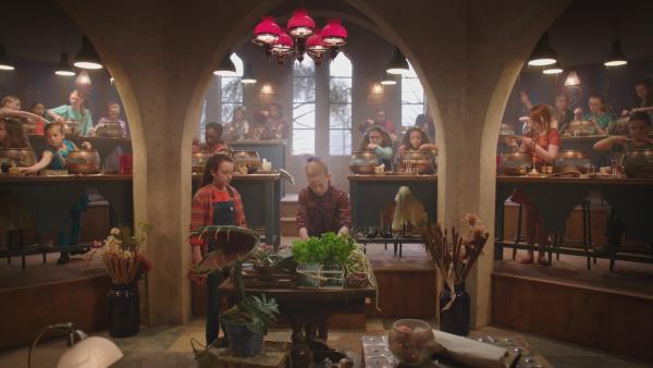Auf der Graustein-Akademie ist der praktische Teil der Aufnahmeprüfung, das Zaubertrankbrauen, in vollem Gang. Mildred (Bella Ramsey, l.) und Esther (Jenny Richardson, r.) holen sich noch Zutaten für ihren Trank. | Rechte: ZDF/BBC/ZDF Enterprises
