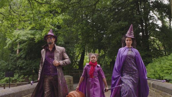 Edith Nachtschatten (Tamara Smart, M.), die Tochter eines glamourösen Zauberehepaars, kommt neu an die Akademie.  (Vater: Jonathan Ojinnaka, l., Mutter: Holly Quin-Ankrah, r.) | Rechte: ZDF/BBC/ZDF Enterprises