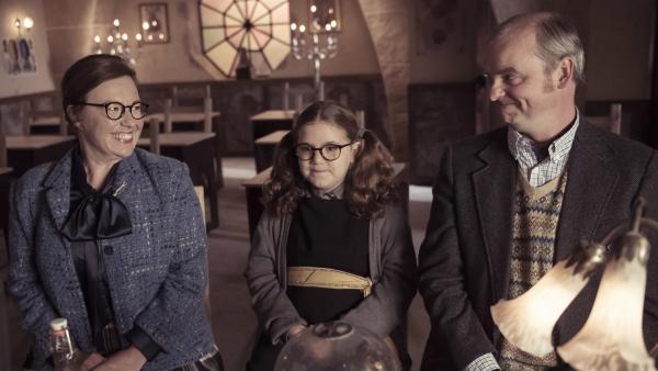 Es ist Elternabend an der Graustein-Akademie und Maude (Meibh Campbell, M.) ist gespannt, ob ihr Vergessenszauber gewirkt hat. Ob alle Lehrer ihre Missetaten vergessen haben, so dass ihre Eltern (Lynsey-Anne Moffat, l. und  Henry Miller, r.) stolz auf sie sein können. | Rechte: ZDF/James Stack/BBC/ZDF Enterprises