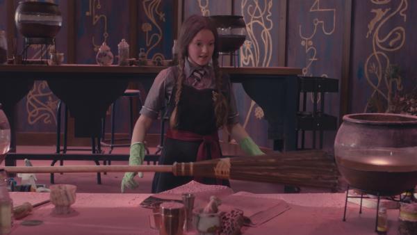 Mildred (Bella Ramsey) muss das Labor saubermachen, das sie und Indigo mit rosa Wiederbelebungsstaub verschmutzt haben. Natürlich ging mal wieder ein Zauberspruch daneben. Da kommt ihr die Idee, den Besen wiederzubeleben, damit er ihr beim Putzen helfen kann. | Rechte: ZDF/CBBC/ZDF Enterprises