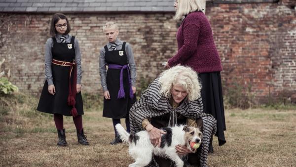 Clarissa (Kitty Slack, l.) und Sybille (Trixie Hyde, 2.v.l.) können es irgendwie nicht glauben: Angeblich soll Stern, der Hund, dieser merkwürdigen Frau Zelda Zunderwink (Gilian Cally, 2.v.r.) gehören. Frau Graustein (Clare Higgins, r.) bittet die beiden Mädchen, Mildred und Indigo zu holen, damit die sich vom Hund verabschieden können. | Rechte: ZDF/James Stack