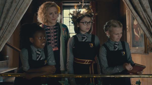 Die drei Freundinnen - Beatrix (Ynez Williams, l.) , Clarissa (Kitty Slack, 2.v.r.) und Sybille (Trixie Hyde, r.) - führen zusammen mit Mildreds Mutter (Nicola Stephenson) den vermeintlichen Standesbeamten durch die Trauung. Diejenige, die den leuchtenden Kranz auf dem Kopf hat, kann die Kommandos geben, die der verzauberte nicht-magische Wanderer, den die Mädels aus Versehen an der Bushaltestelle abgeholt haben, wie ferngesteuert ausführt.   Rechte: ZDF/CBBC/ZDF Enterprises 2019