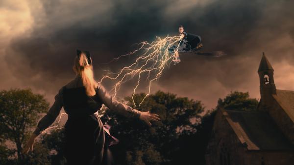 Esther (Jenny Richardson, l.) traut sich gegen die bedrohliche Indigo (Kelsey Calladine-Smith, r.) anzutreten, dafür hat sie sich mit einem Schutzzauber gegen die Blitze abgeschirmt. Ist Esther tatsächlich so mutig, oder hat sie sich diese Situation mit dem geklauten Wunschstern gewünscht, um nachher als Retterin dazustehen? | Rechte: ZDF/CBBC/ZDF Enterprises 2019