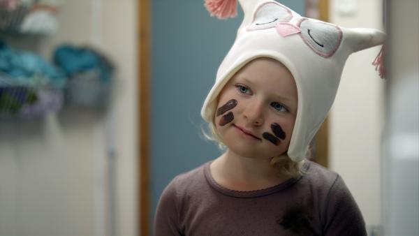 Sol (Olivia Jørgensen) nimmt sich Linneas Eulenmütze und malt sich das Gesicht braun. Sie spielt, dass sie eine Eule ist.   Rechte: KiKA/NRK