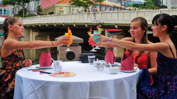 Ein Abschieds -Toast in Singapur v.li.n.re.: Emma (Sophie Karbjinski), Ally (Marny Kennedy) und Jackie (Charlotte Nicdao) | Rechte: NDR/Southern Star